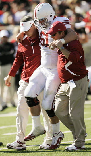 OU's Ben Habern (61) is helped off the field during the college football game between the University of Oklahoma Sooners (OU) and the Texas Tech University Red Raiders (TTU) at Jones AT&T Stadium in Lubbock, Texas, Saturday, Nov. 21, 2009. Photo by Nate Billings, The Oklahoman