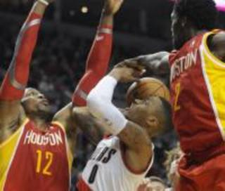 Houston Rockets' Dwight Howard (12) and Patrick Beverley (2) defend against Portland Trail Blazers' Damian Lillard (0) during the second half of an NBA basketball game in Portland, Ore.,Thursday Dec. 12, 2013. Portland beat the Rockets 111-104. (AP Photo/Greg Wahl-Stephens)