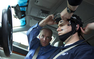 Russ Martin of triple A, is assisted by Joel Cooper, left, hooking the electroencephalographic (EEG)-configured skull cap to the research vehicle during a demonstrations in support of their new study on distracted driving in Landover, Md., Tuesday, June 11, 2013. (AP Photo/Manuel Balce Ceneta) ORG XMIT: MDMC110