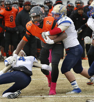 Douglass' Deondre Clark carries and Oologah's Drake Barnes (4) and Trent Harris (27) defend in high school football playoff action on Saturday, Nov. 23, 2013, in Oklahoma City, Okla. Photo by Steve Sisney, The Oklahoman