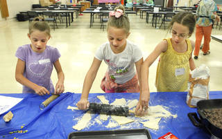 """Grace Hanson, 8, Lillian Greene, 10, and Stefi Thanscheidt, 10, roll out dough for a taco recipe at the """"Kids in the Kitchen"""" workshop. Photo by David McDaniel, The Oklahoman David McDaniel -"""