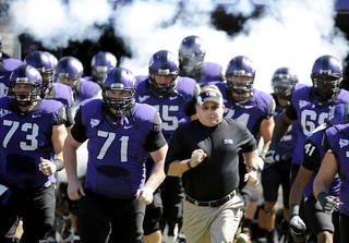 In this photo taken Saturday, Oct. 1, 2011, TCU head coach Gary Patterson runs onto the field with his team before an NCAA college football game against SMU in Fort Worth, Texas. Leaders of the Big 12 Conference cleared the way Thursday, Oct. 6, 2011, to add TCU, a move that would bring in a rising program and potentially shore up a league that seemed ready to fall apart just a few weeks ago. (AP Photo/Matt Strasen) ORG XMIT: NY169