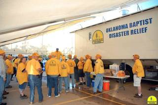 Members of Oklahoma Baptist Disaster Relief gather for a meeting outside one of the relief organization's mobile kitchens. Photo provided