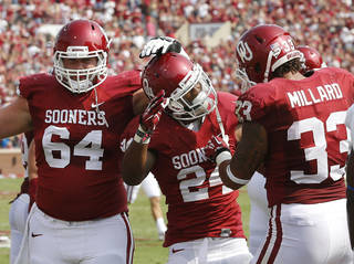 Oklahoma running back Brennan Clay (24) is congratulated by offensive lineman Gabe Ikard (64) and fullback Trey Millard (33) following his touchdown against Tulsa in the first quarter of an NCAA college football game in Norman, Okla., Saturday, Sept. 14, 2013. (AP Photo/Sue Ogrocki) ORG XMIT: OKSO109