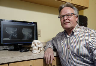 Dr. Steven Sullivan uses models and X-rays to explain corrective jaw surgery. Photo by Sarah Phipps, The Oklahoman