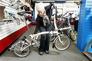 Ann Ryan, co-owner of Al's Bicycles, unfolds a Brompton bicycle as she explains how the folding bicycles work and why they are gaining popularity.