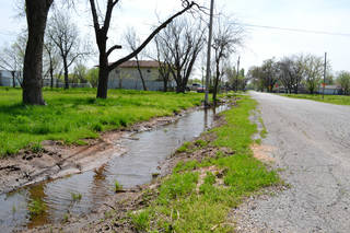 Standing water fills a ditch in Crutcho on Wednesday, March 28, 2012, a week after heavy rains hit the area. ZEKE CAMPFIELD - The Oklahoman