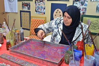 Nuran Oner, an official state artist of Turkey, demonstrates the art of water marbling. She lives in Ankara, Turkey, and traveled to Oklahoma City for the Turkish Festival presented by the Raindrop Foundation on Saturday and Sunday. Photo by M. Tim Blake, for The Oklahoman M. Tim Blake