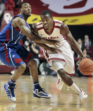 Oklahoma Sooner Sam Grooms (1) dribbles past Kansas Jayhawk Naadir Tharpe (1) as the University of Oklahoma (OU) Sooners play the Kansas Jayhawks in men's college basketball at the Lloyd Noble Center on Saturday, Jan. 7, 2012, in Norman, Okla. Photo by Steve Sisney, The Oklahoman