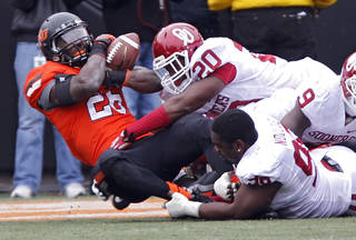 Oklahoma's Frank Shannon (20) and Chuka Ndulue (98) stop Oklahoma State's Desmond Roland (26) during the Bedlam college football game between the Oklahoma State University Cowboys (OSU) and the University of Oklahoma Sooners (OU) at Boone Pickens Stadium in Stillwater, Okla., Saturday, Dec. 7, 2013. Photo by Chris Landsberger, The Oklahoman