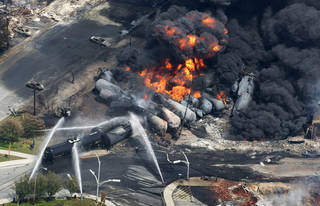 Smoke rises from railway cars carrying crude oil July 6, 2013, after derailing in downtown Lac Megantic, Quebec. AP File Photo Paul Chiasson