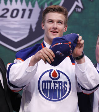 Oscar Klefbom, of Sweden, puts on a hat after he was drafted by the Edmonton Oilers in the first round of the National Hockey League entry draft, Friday June, 24, 2011, in St. Paul, Minn. (AP Photo/Andy King)