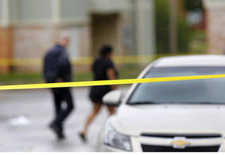 A police officer and a woman walk inside an area marked off with crime scene tape. Oklahoma City police are seeking the public's help in investigating a double homicide Wednesday in northwest Oklahoma City. Photo by Jim Beckel, The Oklahoman Jim Beckel