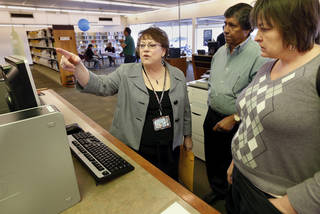 Almonte Library Manager LaVetta Dent explains operation of the computer reservation system to Jay Ramanjula and Dana Tuley-Williams during the grand reopening of the library. Photos by Steve Sisney, The Oklahoman