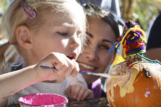 Left: Kaitlyn Zabrocki, 4, of Edmond, plasters her pumpkin with white and yellow paint while her mom, Amanda, looks on Saturday at the Myriad Botanical Gardens. Photos by Zeke Campfield, The Oklahoman