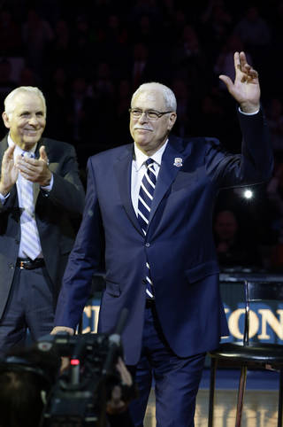 Phil Jackson waves to the crowd as former teammate Jerry Lucas, left, claps during a halftime ceremony to honor the 1972-73 New York Knicks at an NBA basketball game between the Knicks and the Milwaukee Bucks, Friday, April 5, 2013, in New York. (AP Photo/Frank Franklin II) ORG XMIT: MSG114
