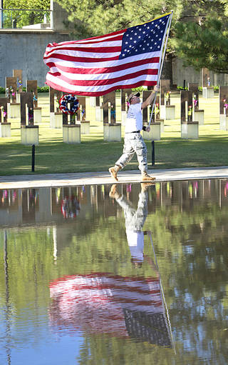 Retired Staff Sargent Ted Bryan Krey carries a flag by the reflecting pool during the 18th Anniversary Remembrance Ceremony at the Oklahoma City National Memorial and Museum, Friday, April 19, 2013. Photo By David McDaniel/The Oklahoman