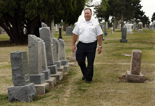 Deputy Fire Chief Jim Bailey walks past grave markers near the location of a mass, unmarked gravesite discovered at the IOOF Cemetery in Norman, where the victims of a 1918 fire are believed to be buried. PHOTOs BY STEVE SISNEY, THE OKLAHOMAN STEVE SISNEY