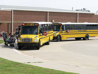 Deer Creek Elementary School students prepare to board buses Monday. The district is considering a teaching plan that could delay the start of school one day each week. Photo by Vallery Brown, THE OKLAHOMAN