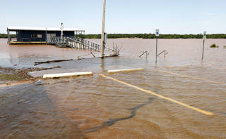 The parking lot and walkway to the fishing dock at Spring Creek Park at Arcadia Lake were covered by water after the lake flooded following Friday night's storms. PHOTO BY PAUL HELLSTERN, THE OKLAHOMAN. PAUL HELLSTERN - THE OKLAHOMAN