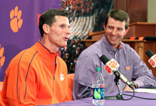 Clemson head football Dabo Swinney, right, reacts as Brent Venables, left, answers a question during an NCAA college football news conference where he was introduced as the new defensive coordinator at Clemson, on Friday, Jan. 20, 2012, in Clemson, S.C. (AP Photo/The Independent-Mail, Mark Crammer) THE GREENVILLE NEWS OUT, SENECA NEWS OUT ORG XMIT: SCAND108