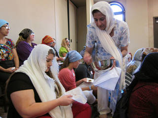 Indira Singh, an Oklahoma City pediatrician, gives prasad, a religious food offering typically given to Sikh worshippers, to Casady School student Natasha Spicer, 17, during an Interfaith Youth Tour presentation on Sikhism at the Sikh Gurdwara of Oklahoma. Carla Hinton - The Oklahoman