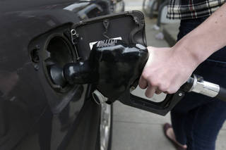 A customer fills her car with fuel at a gas station in Brookline, Mass. AP Photo Steven Senne - AP