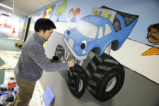 """Shikoh Shiraiwa with Palmer Studios paints a racetrack-theme mural inside Oakcrest Church of Christ, 1111 SW 89, in conjunction with the church's children ministry the """"Starting Line KIds."""" PAUL B. SOUTHERLAND - PAUL B. SOUTHERLAND"""