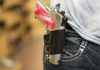 Brigette Blackwell demonstrates at Big Boys Guns and Ammo on Tuesday the type of holster that could be used to openly carry a pistol. Photo By Steve Gooch, The Oklahoman
