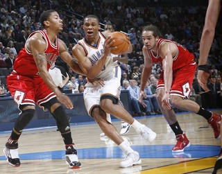 Russell Westbrook, middle, drives past Chicago's Derrick Rose, left, and Joakim Noah during last year's game on Jan. 27. The two teams play tonight in their NBA season opener. PHOTO BY CHRIS LANDSBERGER, THE OKLAHOMAN