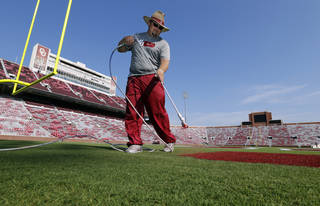 Jeff Salmond, Director of Athletics Fields, takes his turn as roundskeepers paint the field in preparation for Saturday's season opener for the University of Oklahoma Sooners at Gaylord Family-Oklahoma Memorial Stadium in Norman, Okla., on Wednesday, Aug. 28, 2014. Photo by Steve Sisney, The Oklahoman