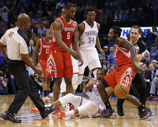 Oklahoma City Thunder guard Russell Westbrook, bottom, reacts after a foul by Houston Rockets guard Pat Beverley, right, during the first quarter of an NBA basketball game in Oklahoma City, Tuesday, March 11, 2014. Looking on are Rockets forward Terrence Jones (6) and Thunder center Hasheem Thabeet (34). (AP Photo/Sue Ogrocki)