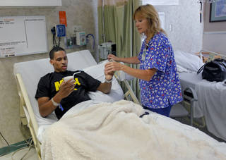 Bricktown shooting victim Norman Richards, 22, is given medicine by Debbie Foyil, RN, as he awaits discharge from Jim Thorpe Rehabilitation Hospital on Friday, June 22, 2012. Photo by Chris Landsberger, The Oklahoman CHRIS LANDSBERGER - CHRIS LANDSBERGER