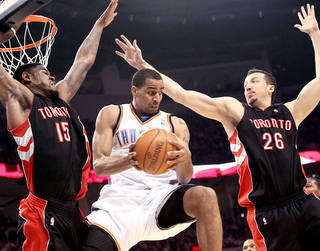 Oklahoma City's Thabo Sefolosha looks for room in front of pressure from Toronto's Amir Johnson, left, and Hedo Turkoglu during the Thunder's 119-99 win Sunday. PHOTO BY JOHN CLANTON, THE OKLAHOMAN