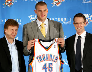 Rookie Thunder center Cole Aldrich, center, holds his Oklahoma City jersey with coach Scott Brooks and general manager Sam Presti. PHOTO BY JOHN CLANTON, THE OKLAHOMAN