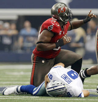 Tampa Bay Buccaneers defensive tackle Gerald McCoy, top, celebrates after teammate Michael Bennett sacked Dallas Cowboys quarterback Tony Romo (9) during the first half of an NFL football game on Sunday, Sept. 23, 2012, in Arlington, Texas. (AP Photo/LM Otero)