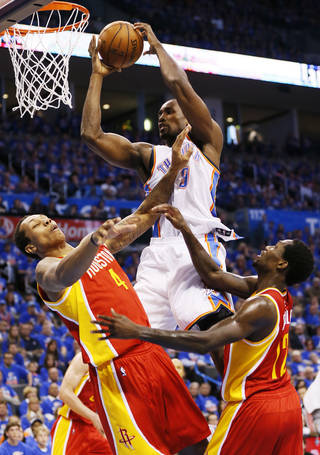 Oklahoma City's Serge Ibaka (9) grabs a rebound between Houston's Greg Smith (4) and Patrick Beverley (12) in the second half during Game 5 in the first round of the NBA playoffs between the Oklahoma City Thunder and the Houston Rockets at Chesapeake Energy Arena in Oklahoma City, Wednesday, May 1, 2013. Houston won, 107-100. Photo by Nate Billings, The Oklahoman