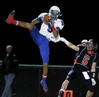 Millwood wide receiver Brandon Swindall, left, pulls down a catch past Verdigris defensive back Jay Sparkman, during the Class 2A quarterfinal match-up in Verdigris on Nov. 27, 2009. Photo by Cory Young, Tulsa World
