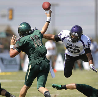 Bison quarterback Blake Woodard releases this pass just before being hit by Southwestern College linebacker Paul Mata in the first half. The Oklahoma Baptist University football team took to the field on the school's Shawnee campus for the first time in more than seven decades when they hosted the Southwestern College(Kansas) Moundbuilders at Bison Field in the Eddie Hurt Athletic Center on Saturday, Aug. 31, 2013. The Bison team was defeated today, 26-22. Prior to the 2013 season opener, the Bison football team played their last game in 1940. Photo by Jim Beckel, The Oklahoman. The Oklahoma Baptist University football team took to the field on the school's Shawnee campus for the first time in more than seven decades when they hosted the Southwestern College(Kansas) Moundbuilders at Bison Field in the Eddie Hurt Athletyic Center on Saturday, Aug. 31, 2013. The Bison team was defeated today, 26-22. Prior to the 2013 season opener, the Bison football team played their last game in 1940. Photo by Jim Beckel, The Oklahoman.