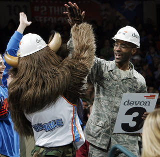 Damont Cooley, a staff sergeant in the US Air Force, high-fives Rumble the Bison during Military Night at the NBA basketball game between the Oklahoma City Thunder and the New York Knicks at the Ford Center in Oklahoma City, January 11, 2010. Photo by Nate Billings, The Oklahoman
