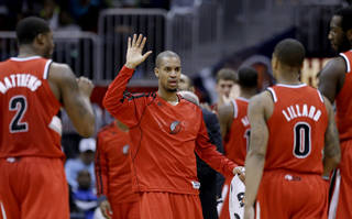 Portland Trail Blazers' Eric Maynor, center, greets teammates, from left, Wesley Matthews, Damian Lillard, and J.J. Hickson, as they come off the court for a timeout in the fourth quarter of an NBA basketball game against the Atlanta Hawks, Friday, March 22, 2013, in Atlanta. Portland won 104-93. (AP Photo/David Goldman) ORG XMIT: GADG114
