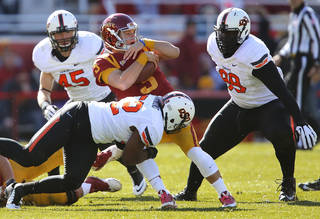 Oklahoma State 's Ryan Simmons (52) brings down Iowa State's Grant Rohach (3) during the college football game between the Oklahoma State University Cowboys (OSU) and the Iowa State University Cyclones (ISU) at Jack Trice Stadium in Ames, Iowa, on Saturday, Oct. 26, 2013. Photo by Chris Landsberger, The Oklahoman