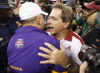 Alabama head coach Nick Saban, right, talks to LSU head coach Les Miles after the BCS National Championship college football game Monday, Jan. 9, 2012, in New Orleans. Alabama won 21-0. (AP Photo/Dave Martin) ORG XMIT: BCS187