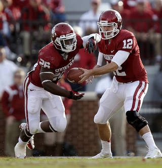 Oklahoma's Landry Jones (12) hands the ball off to Damien Williams (26) during the college football game between the University of Oklahoma Sooners (OU) and Baylor University Bears (BU) at Gaylord Family - Oklahoma Memorial Stadium on Saturday, Nov. 10, 2012, in Norman, Okla. Photo by Chris Landsberger, The Oklahoman