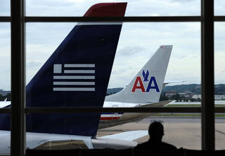 An American Airlines plane and a US Airways plane are parked at Washington's Ronald Reagan National Airport in Washington. AP File Photo Susan Walsh -
