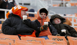Oklahoma State fans stay warm before the Bedlam college football game between the Oklahoma State University Cowboys (OSU) and the University of Oklahoma Sooners (OU) at Boone Pickens Stadium in Stillwater, Okla., Saturday, Dec. 7, 2013. Photo by Bryan Terry, The Oklahoman