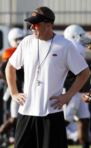 OKLAHOMA STATE UNIVERSITY / OSU / COLLEGE FOOTBALL: Oklahoma State defensive coordinator Glenn Spencer watches over drills during the first full pad practice of the fall on August 6, 2013. Photo by KT King/ for The Oklahoman