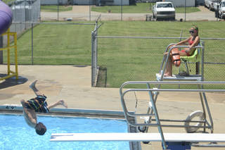 Lifeguard Joy Groncki, 19, watches as a child goes off the diving board at the Stillwater Municipal Pool. PHOTO BY ADAM KEMP, THE OKLAHOMAN