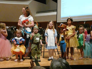Children dressed as Disney characters line the stage at Catlett Music Center in a costume parade Sunday before a concert celebrating a Disney exhibit at the Fred Jones Jr. Museum of Art in Norman. PHOTOS BY CONNIE HEFNER, FOR THE OKLAHOMAN