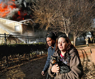 """Frightened and dazed after being awakened by a firefighter telling her to get out of her house, Amanda Miller, a resident at Quail Springs Condominiums, carries her pet, Lola, to a place of safety as units in her complex burn behind her. Miller said she was taking a nap when a fireman kicked open her door and shouted for anyone inside to leave the building immediately because it was on fire. Miller said she hurriedly put on sweat pants and a hooded sweatshirt, grabbed her purse, picked up her dog and ran out of her house. she said, """"I didn't have time to grab nothing."""" As she knelt on the grass watching the units burn, she sobbed and said she was """"watching my whole life go up in smoke."""" Miller and her husband, a disabled Army veteran, lived in the condominium with their dog. Oklahoma City firefighters battled a four-alarm blaze for more than an hour at Quail Springs Condominiums, 14415 N Pennsylvania, before extinguishing most of the flames. Around 3 p.m. on Tuesday, Dec. 31, 2013, fire units were dispatched to the complex, just north of Memorial Road. A chief at the scene said high winds presented additional problems for firefighters as they worked to keep the fire from spreading to other units. Photo by Jim Beckel, The Oklahoman"""